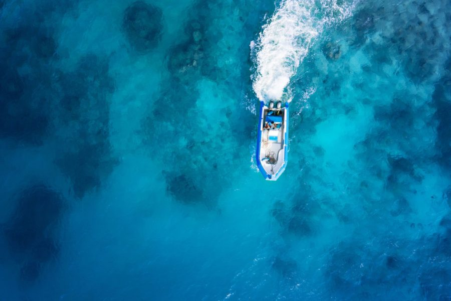 Overhead view of boat speeding on blue water